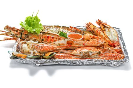 Grilled Mixed Seafood Big Set: Lobster Fish Blue Clabs Big Shrimps Mussels Clams Calamari Squids with pieces of lemon & vegetable on white background with shadow Macro Close up low angle side view. Stock fotó