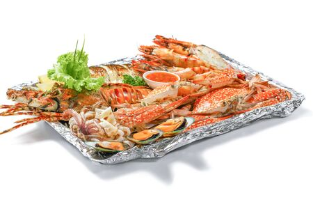 Grilled Mixed Sea-food Platter Set contain Lobster, Fish, Blue Clab, Big Prawn, Mussel Clam and Calamari Squid with piece of lemon & vegetable isolated on white background with shadow, High angle view