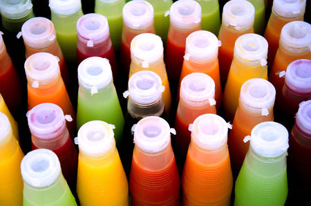 Assortment of cold tropical fruit juice in bottles photo