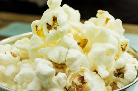 cuisine entertainment: Cropped Popcorn in a silver bowl over wood background