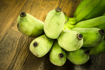 yellow  green: Green banana on wooden table, Close up and selective focus Stock Photo