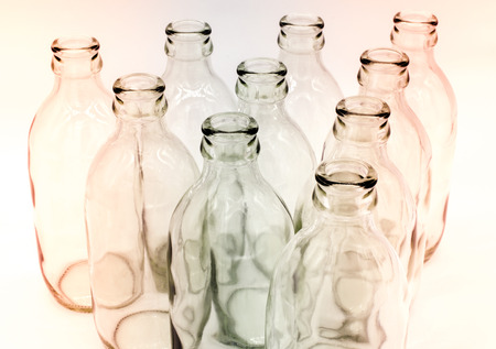 hint: Detail of glass bottles on white background. Hint of red and blue color filter Stock Photo