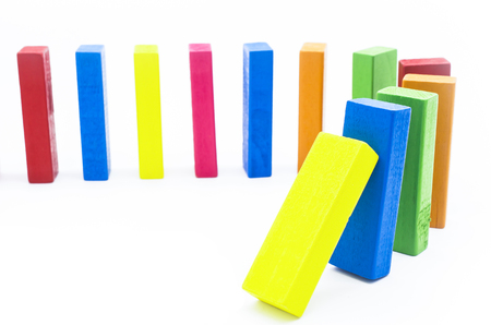 The domino effect of colorful wooden blocks on white background, Selective focus