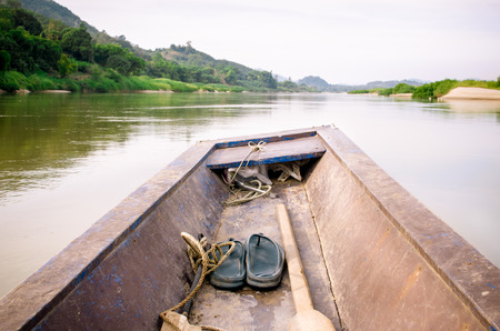 mekong river: Wooden longtail boat heads out into the Mekong River, Thailand and Laos