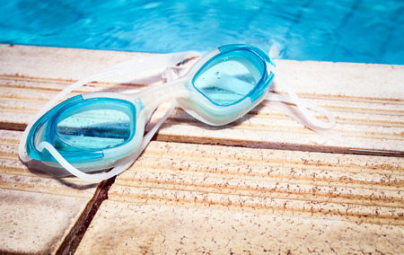 swim goggles: Retro look filter and selective focus  Blue modern Swim goggles on the swimming pool