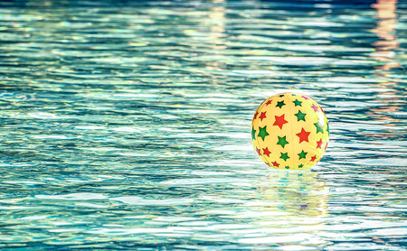 furlough: Retro look filter and selective focus  Inflatable ball floating in swimming pool, With place for your text