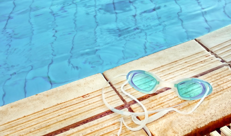 swim goggles: Blue modern Swim goggles on the swimming pool Stock Photo