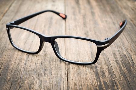 Black eye glasses on wooden floor, Close up image Imagens