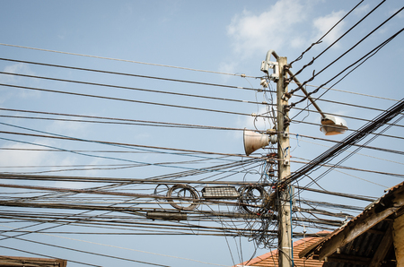 tangling: Confused of Electric post with the blue sky in Bangkok, Thailand Stock Photo