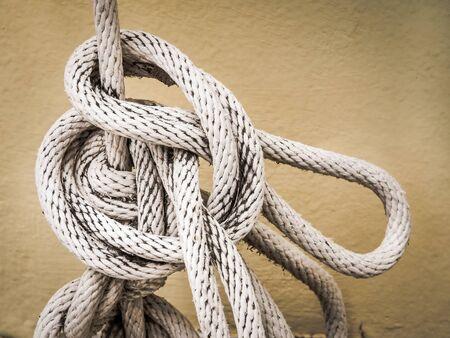 fixed line: Close up of white rope And Knot on yellow cement wall