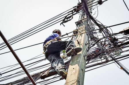 climbing cable: Electricians repairing wire at climbing work on electric post power pole Stock Photo