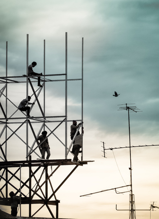 billboard advertising: Silhouette image Group of workers are climbing poles to install billboards. Bangkok, Thailand