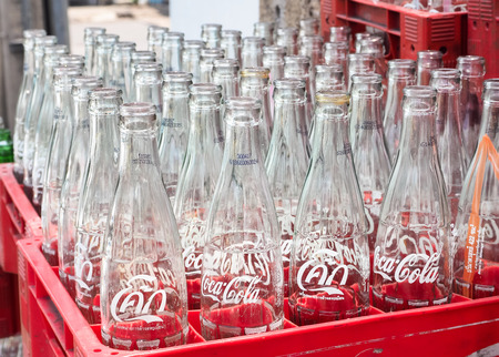 coke bottle: BANGKOK, THAILAND - JUNE 25: Empty recycle bottles of Coca Cola in red plastic box on June 25, 2016 in Bangkok, Thailand. Coca Cola drinks are produced and manufactured by The Coca-Cola Company