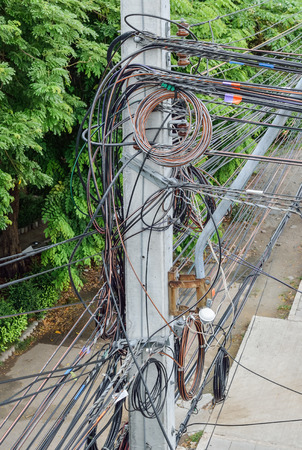 cable tangle: The chaos of cables and wires on every street in Bangkok, Thailand.