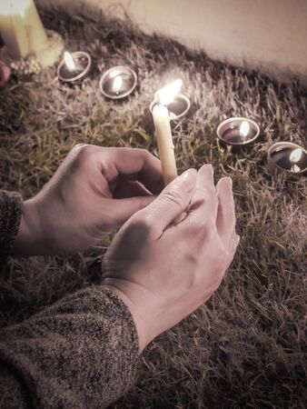 Hands holding candlelight in the night, Retro color filter (hope, pray , sad)