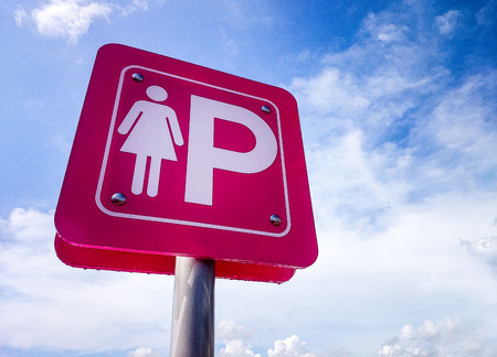 Pink parking sign for lady against the blue sky