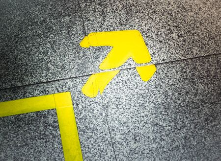 Yellow arrow sign indicate on marble floor, On the subway Stock Photo