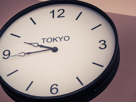 time zone: An airport clock showing Tokyo time zone at 9 past 45, Retro filter color Stock Photo