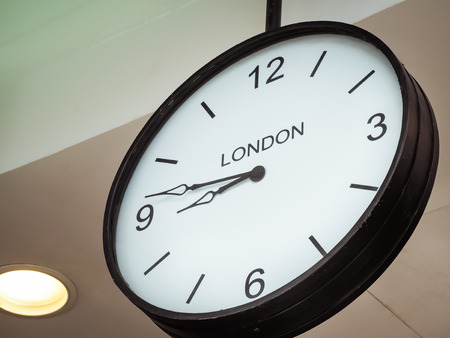 time zone: An airport clock showing London time zone at 9 past 45, Retro filter color