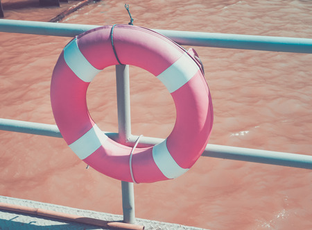 lifebuoy ring hanging on the dock, water safety equipment.