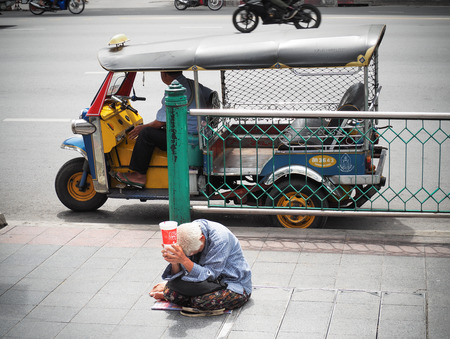 dirty: BANGKOK, THAILAND - AUGUST 9, 2017: Old women beggar begging for donations on the sidewalk in the city, The Main problem encountered in Bangkok and the tourist city in Thailand.