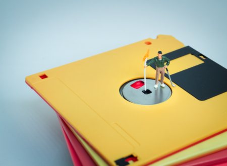 business pitch: Miniature people: Golfer stand on the diskette. Retro filter color Stock Photo