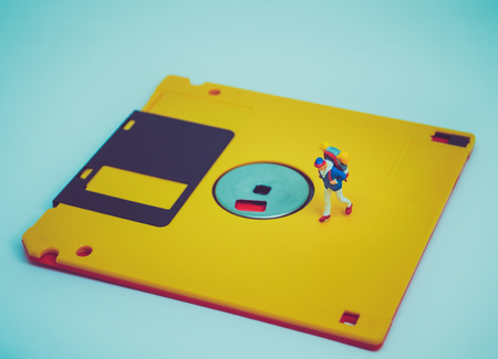 Miniature people: Travelers walk on the old diskette. Retro filter color
