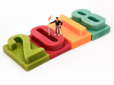 Miniature people: Golfer stand on number of Happy new year 2018