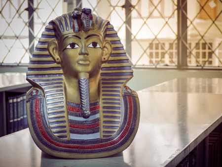 Statues of king pharaoh on a bookshelf with morning light. With place your text. (history, pharaoh, egypt) Stock Photo