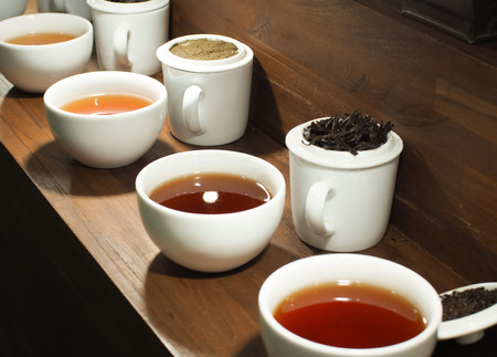 White tea pot and cups with the black tea leaves, Close up image.