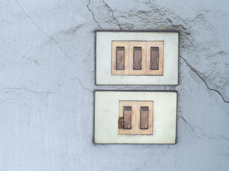 Old switch board with multiple plug switched socket on the wall. Banco de Imagens