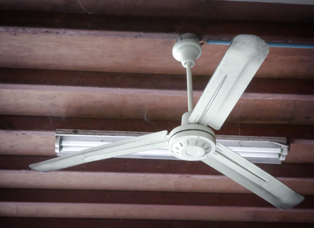 Electric fan is rotating on the wooden ceiling of the old room.