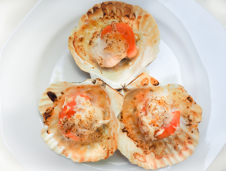 Gegrillte Jakobsmuscheln mit Butter und Käse. Thailändische Meeresfrüchte gegrillte Jakobsmuscheln auf weißem Teller. Standard-Bild