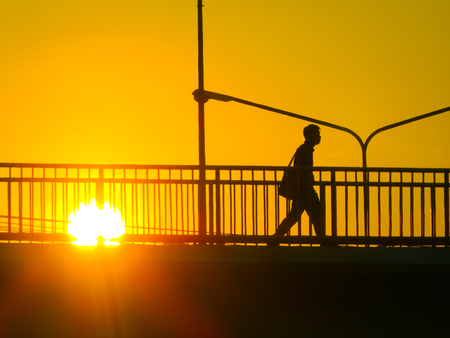 Silhouette of unknown city people walking across the overpass Flyover