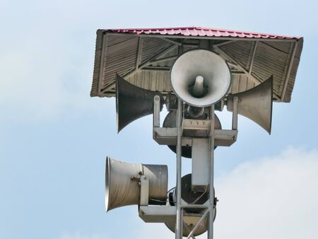 Vintage horn speaker tower with loudspeaker against the sky. System of alert for population. 版權商用圖片