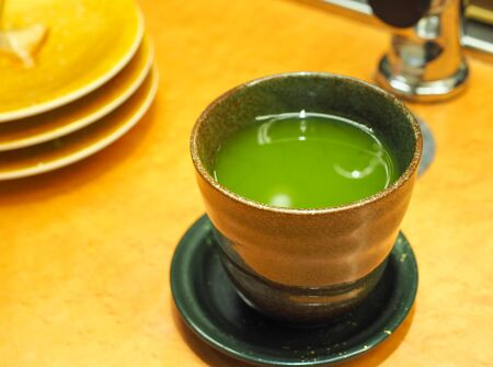 Hot healthy green tea in the Japanese cup on table. Close up and selective focus. Banco de Imagens