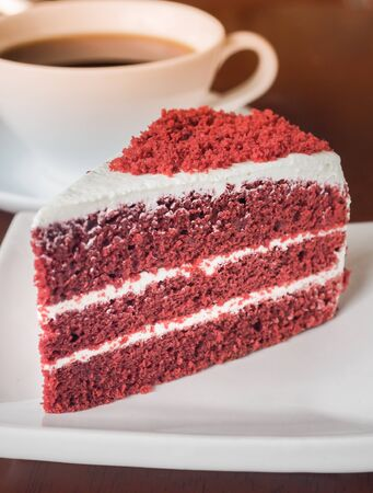 Slice of red velvet cake on a white plate. Close up of red velvet chocolate cake with a cup of hot coffee on table.