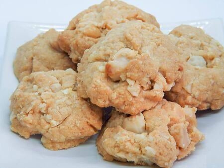 Porzione di biscotti di macadamia su sfondo bianco. Pila di biscotti alle noci di macadamia. Archivio Fotografico