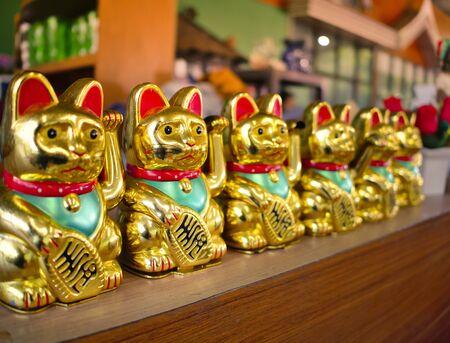 Row of Japanese Lucky Cat or Maneki Neko, Japanese and Chinese Golden Cat dools brings good luck. Stok Fotoğraf