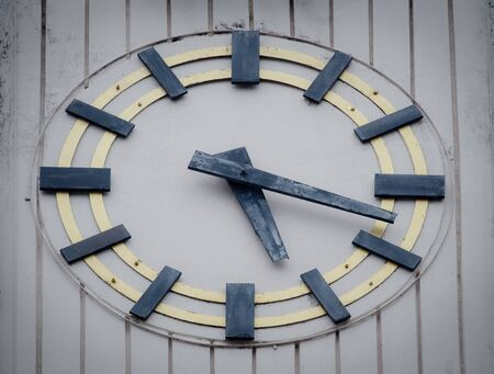 Antique wooden wall clock, installed on the old building wall. Close up image.