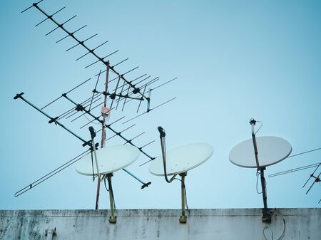 Home satellite dish and TV antenna on top of building, Bangkok, Thailand.