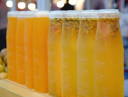 Fresh carrot juice, orange and passion fruit, packed in a ready-to-drink frozen plastic bottle for sale. Reklamní fotografie