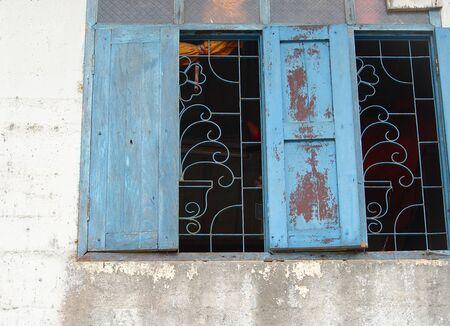 An old blue wooden window on an old peeling wall. Thailand. Stock fotó