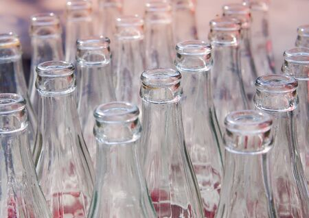 Many used glass bottles arranged in rows. Close up and selective focus of empty soda bottles, Recyclable object image. Stock Photo