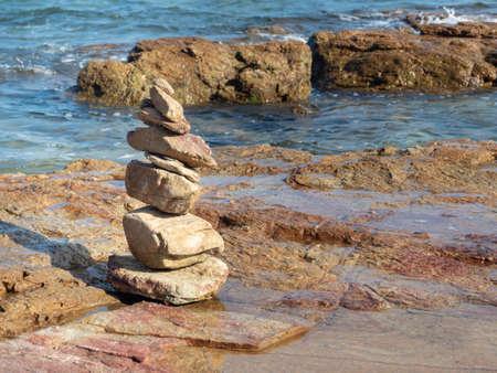 Balanced zen stones on the beach with blue sky and sea background. stones balanced concept Standard-Bild