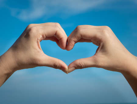 Heart symbol from hands on the blue sky background. Concept for Love or Health. Standard-Bild