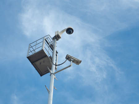 360 Degree fish eye dome CCTV and CCTV camera are installed on column against blue sky.
