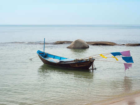 Blue sea with fishing villager boat is docked on the sandy beach.