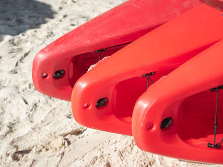 Red canoe or kayak boat are arranged ready to use on the beach.