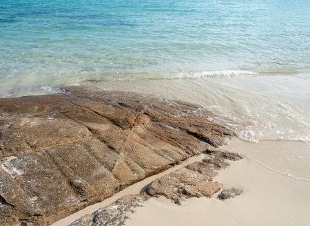 Beautiful natural rocks on the sandy beach and turquoise sea waves. Standard-Bild